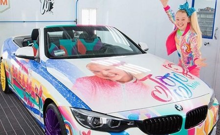 JoJo Siwa in front of her car for her house article.