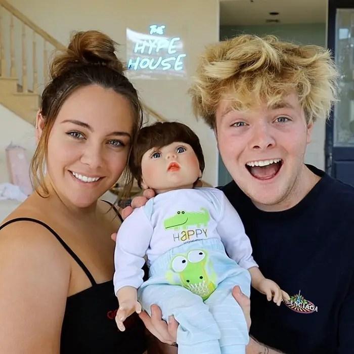 Kouvr Annon and Alex Warren holding a plastic baby.