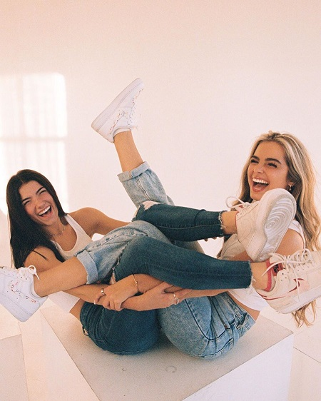 Addison Rae and Charli D'Amelio twisting their legs in a funny way.