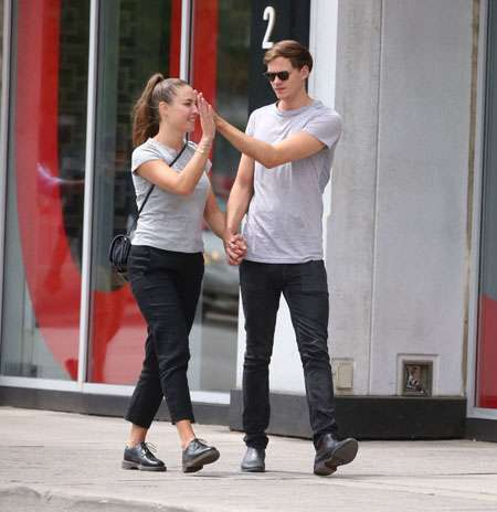 Alida Morberg and Bill Skarsgard high five while walking hand in hand.