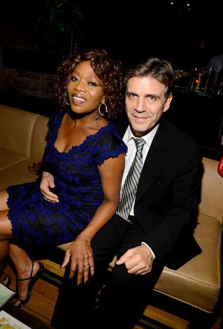 Roderick Spencer with her hand around his wife Alfre, sitting on the couch.