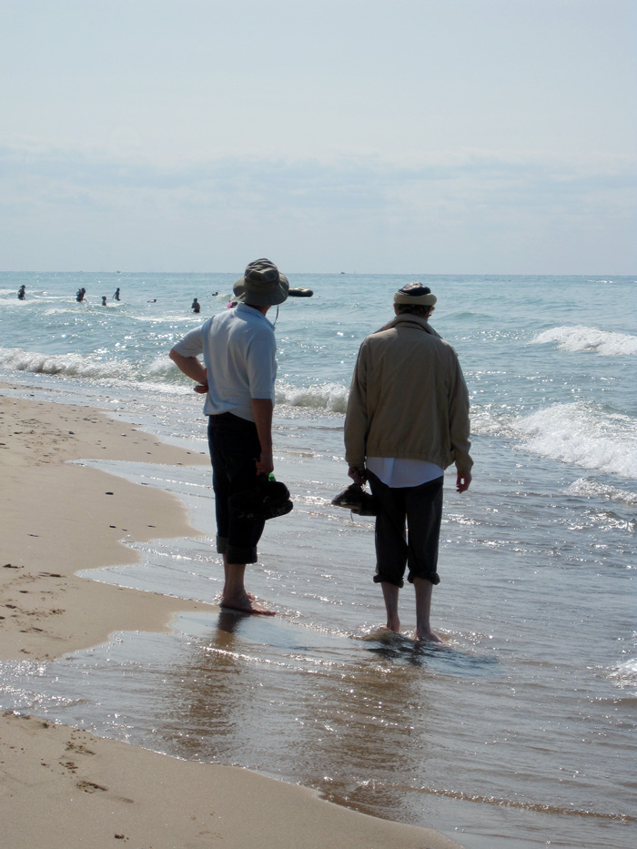 Two men on a beach, © 2013 Celia Her City
