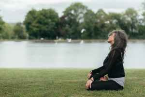 mindful woman sitting in lotus pose on river shore