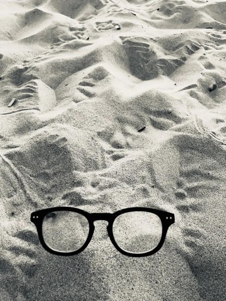 lunettes noires posées sur du sable blanc
