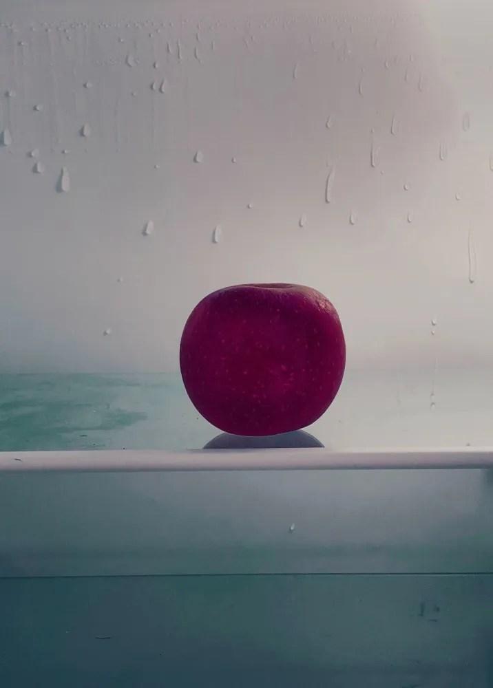 Pomme rouge sur l'étagère d'un frigo dégelé