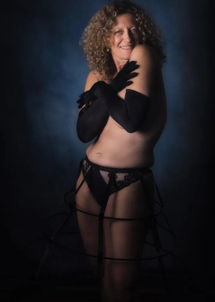 Femme en nu artistique avec crinoline et gants longs noirs tout sourire