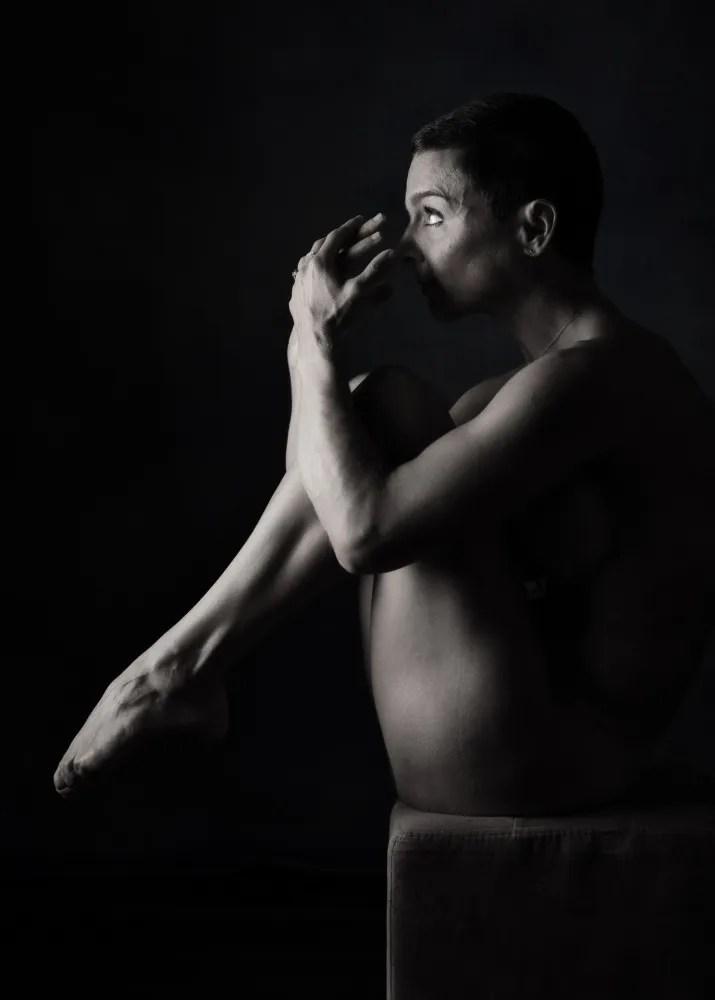 Femme en nu artistique et clair obscur recroquevillée sur un tabouret les mains devant le visage