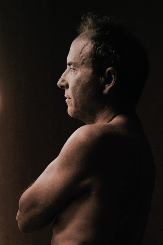 Portrait de profil d'un homme mature en nu artistique et clair obscur