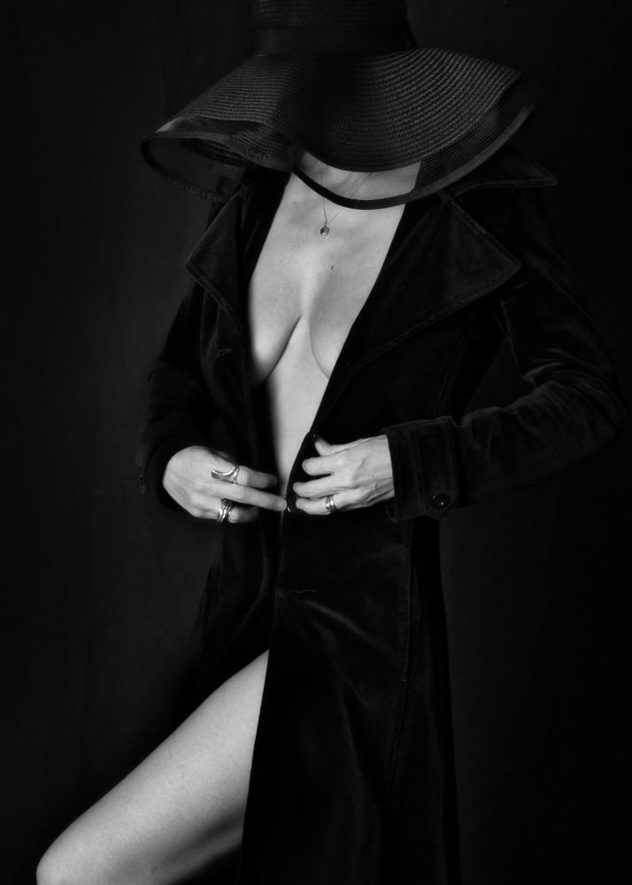 femme nu artistique en noir et blanc et clair obscur portant un chapeau noir et un long manteau noir