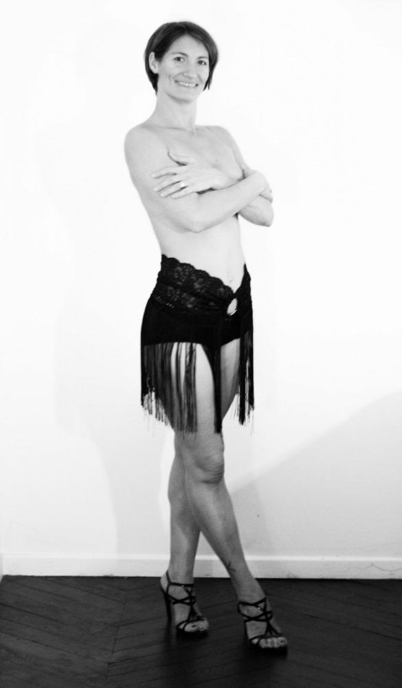 femme en nu artistique debout portant une jupe à franges
