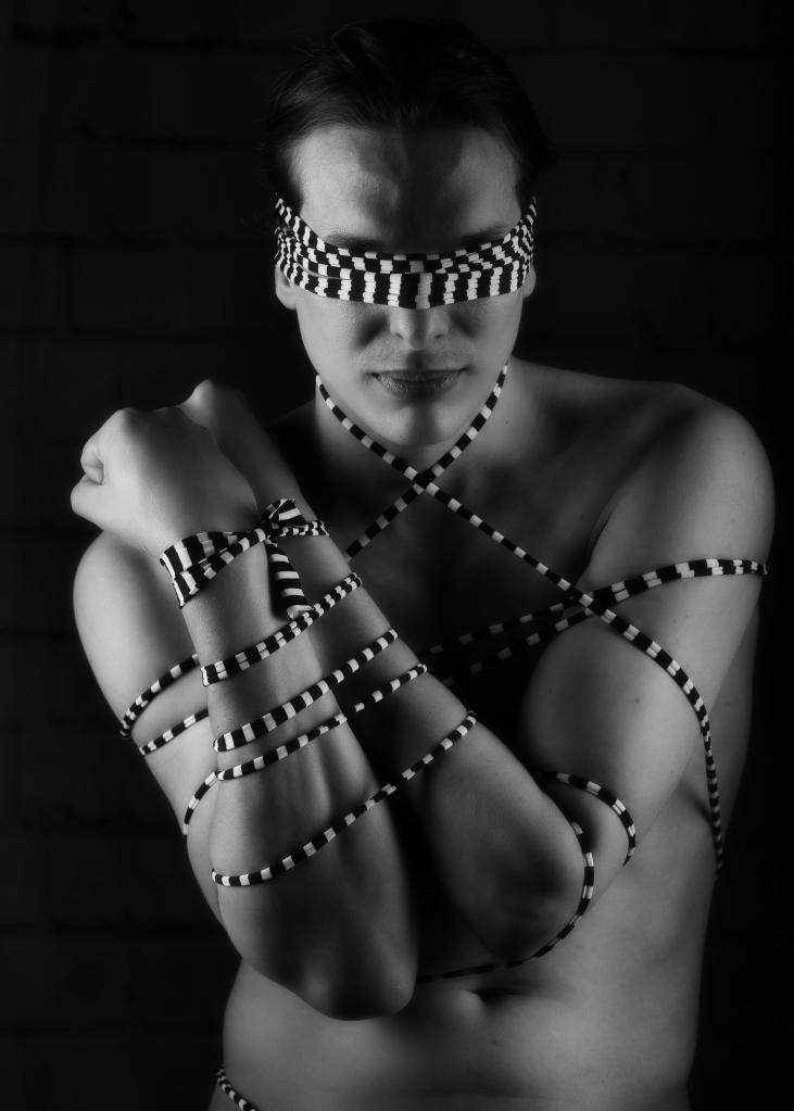 homme en nu artistique noir et blanc et clair obscur attaché par une ficelle en damier