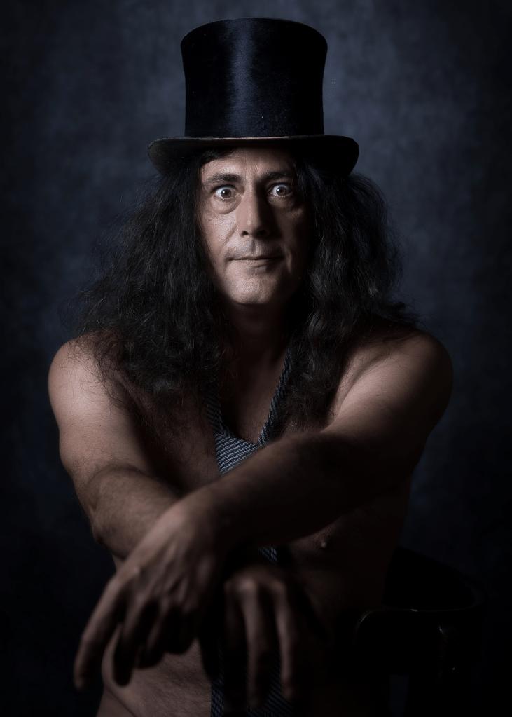 portrait homme aux cheveux longs portant un chapeau haut de forme et ouvrant grand les yeux