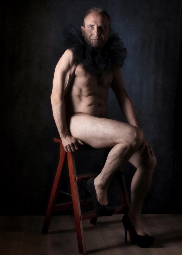 homme mature en nu artistique assis sur un tabouret avec des talons hauts et une collerette de pierrot