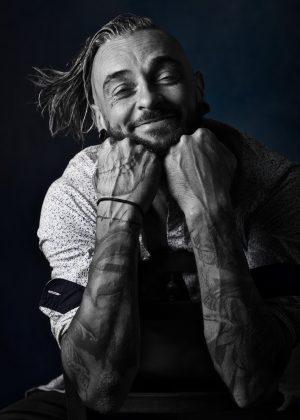 portrait d'un homme tatoué souriant en noir et blanc clair obscur les poings sous le visage