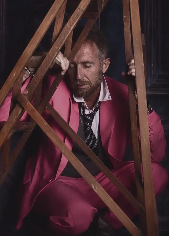 portrait d'un homme barbu en costume rose et cravate sous un escabeau ancien