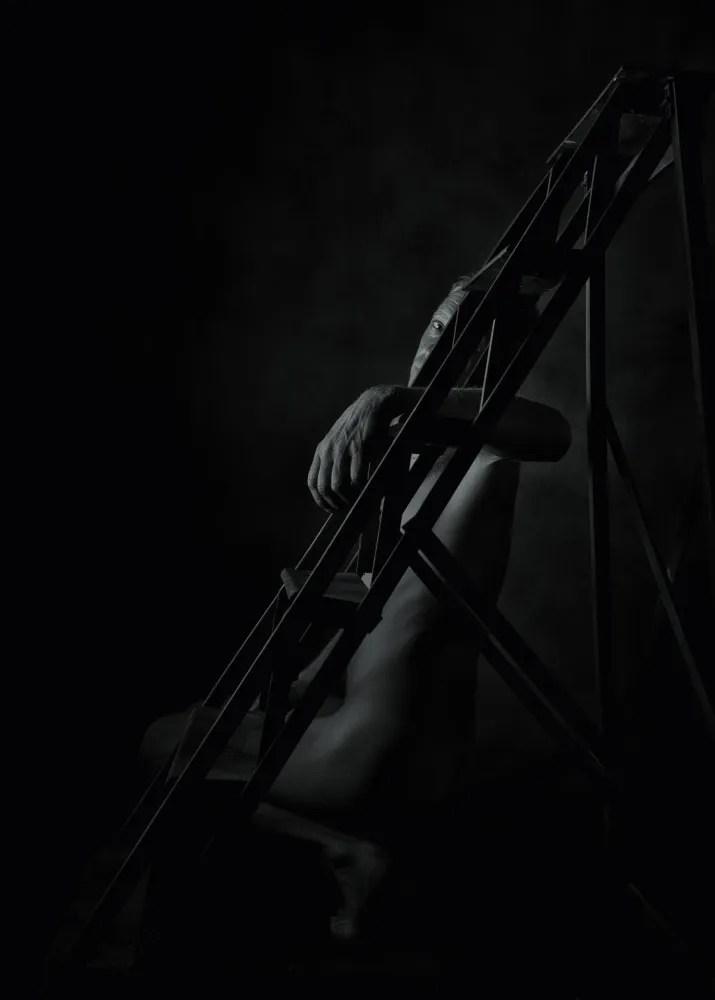 homme en nu artistique clair obscur derrière un escabeau en bois ancien