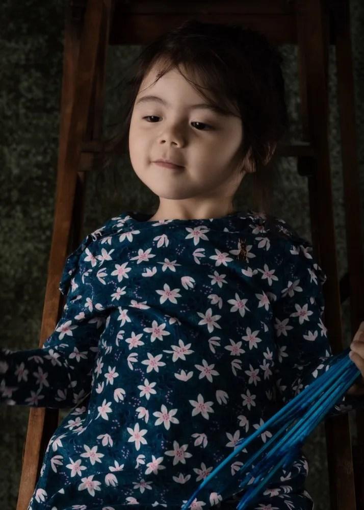 portrait d'une fillette eurasienne les yeux mi clos sur un escabeau en bois