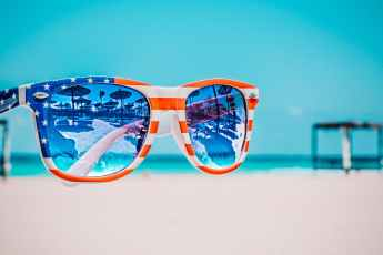 focus photography of american flag accent wayfarer styled sunglasses with sea background