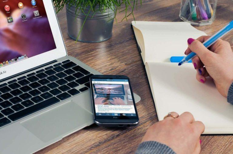 Una mujer sentada frente a su computadora y tiene un cuaderno con pluma lista para escribir y tiene su telefono movil a un lado