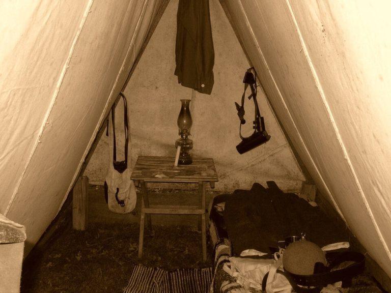 Es una tienda de campana y dentro de ella esta la cama pequena una mesita una lampara de aceite una pistola colgada en la pared y un uniforme de soldado puesto arriba de la cama