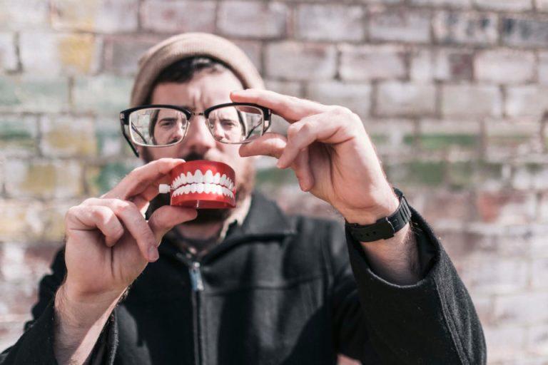 Un hombre tiene una dentadura en sus manos y la esta revisando con sus lentes de aumento