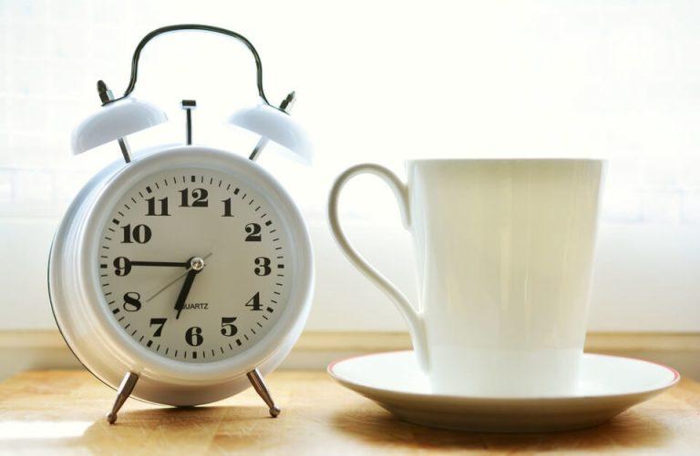 En una mesa esta un reloj redondo blanco con una tasa blanca con cafe
