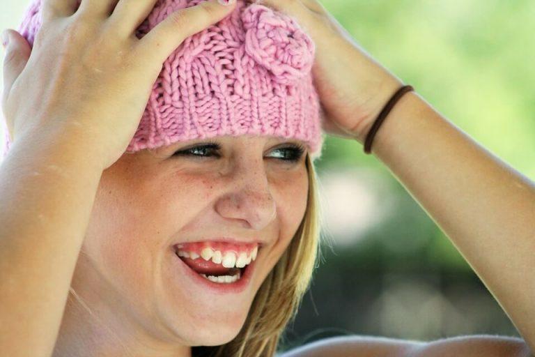 Una jovencitan muy feliz riendose y con sus manos en la cabeza