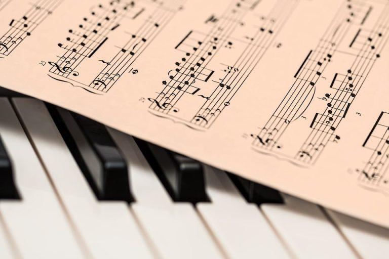 Unas teclas de piano y con una partituraarriba de este