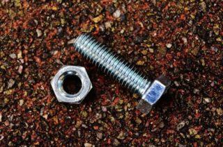 Un tornillo con una tuerca tirados en el suelo de tierra