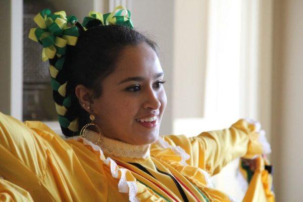 Es una joven sonriente lista para comenzar a bailar el Jarabe tapatio con su vestido mexicano amarillo