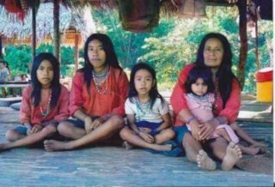Es una madre con cuatro ninas sentadas en el piso bajo la sombra