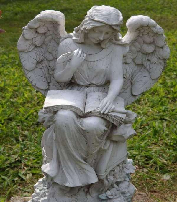 Es un Angel sentado en un jardin escribiendo en un libro