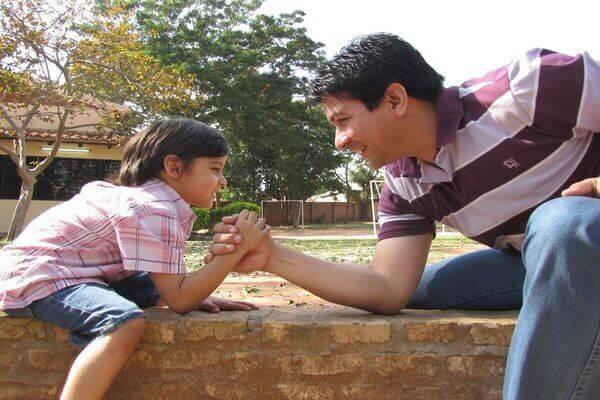 Es una foto del padre con el hijo tomado de una mano y jugando