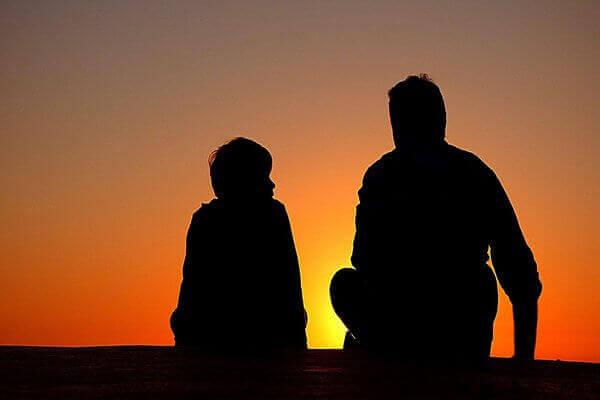 Es una silueta de un padre y su hijo sentados viendo un lindo atardecer
