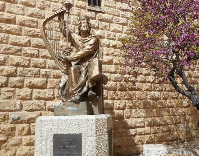 Es una estatua dorada del rey David con un arpa