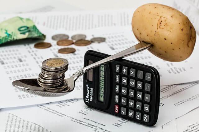 es una cuchara que esta en balance con una calculadora un lado tiene una papa y el otro lado unas monedas