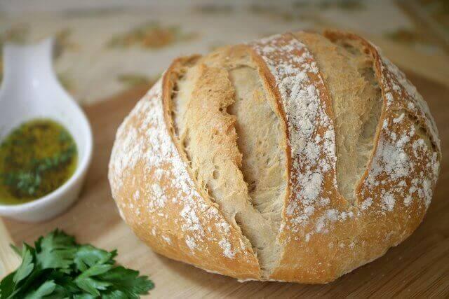 Es una pieza de pan en la mesa con un recipeinte con aceite a un lado