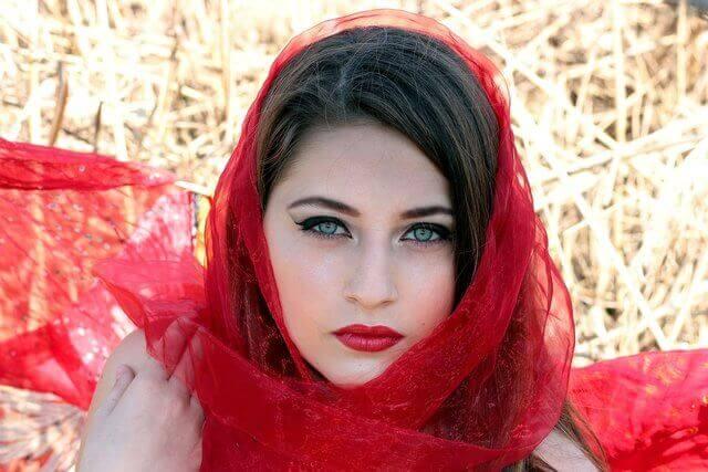 Es el rostro de una mujer bella de ojos color verde y una bufanda color rojo sobre su cabeza