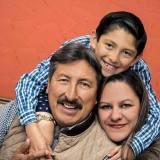 Es una foto de la familia el papa la mama y el hijo sonriendo