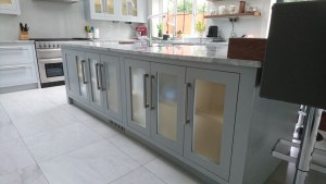 kitchen island cabinets by Celtica Kitchens with frosted glass panels and LED strip lighting