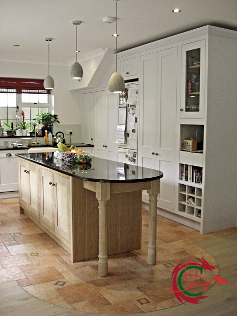 Limed oak kitchen island, granite worktop, tall cabinets and fridge enclosure in painted oak