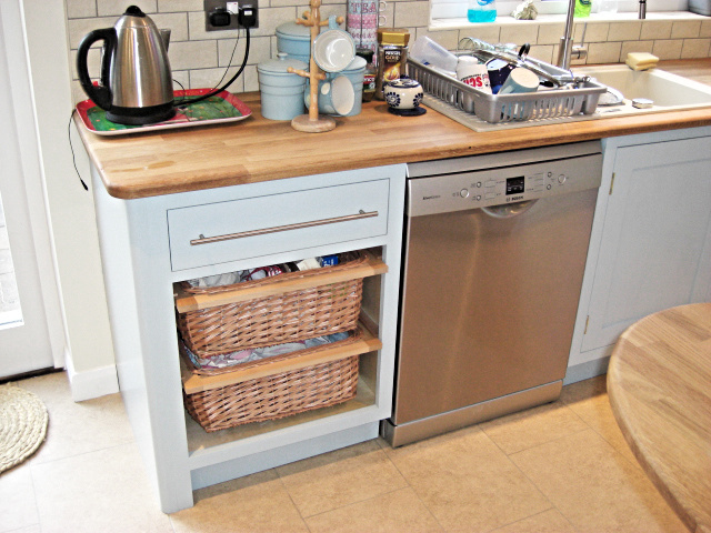 kitchen cabinet with drawer and wicker baskets, oak worktop, stainless steel dishwasher