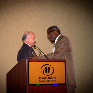 Joseph L. Sherman, president of Rainbow's Board of Directors and president and co-founder of The Reliant Group,  presenting the Affordable Advocate of the Year award to Raynold Richardson, former HUD director, Fort Worth Asset Management Division.