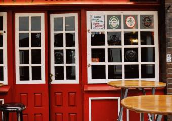 entrance of pub with red door and wooden tables nearby