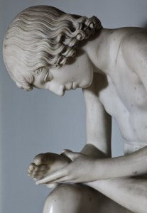 White marble sculpture, Boy pulling a thorn out of his foot ('Spinario') by unknown. 18th century. Marble statue of a boy with a thorn in his foot on a yellow scagliola pedestal on white marble base. from the bronze antique statue, first recorded between 1165/67 outside the Latern Palace and one of the bronzes transferred from there to the Palazzo dei Conservatori (Capitoline Museum) on the Capitol in Romeby Pope Sixtus IV after 1471 where it remains apart from the time it spent in France between 1798 and 1816.