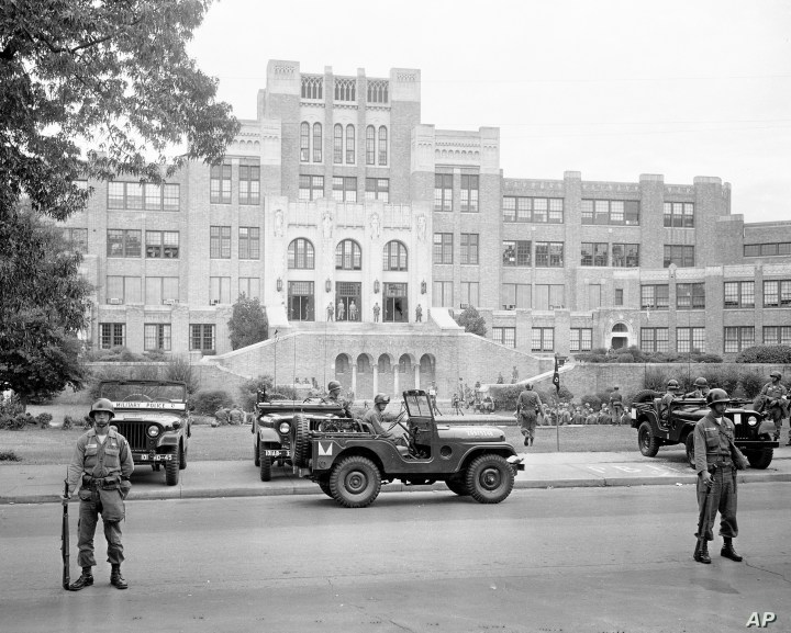 In this Sept. 26, 1957, file photo, members of the 101st Airborne Division take up positions outside Central High School in Little Rock, Ark., after President Dwight D. Eisenhower ordered them into the city to enforce integration at the school.