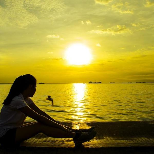 Silhouette of woman stretching by the ocean at sunset.