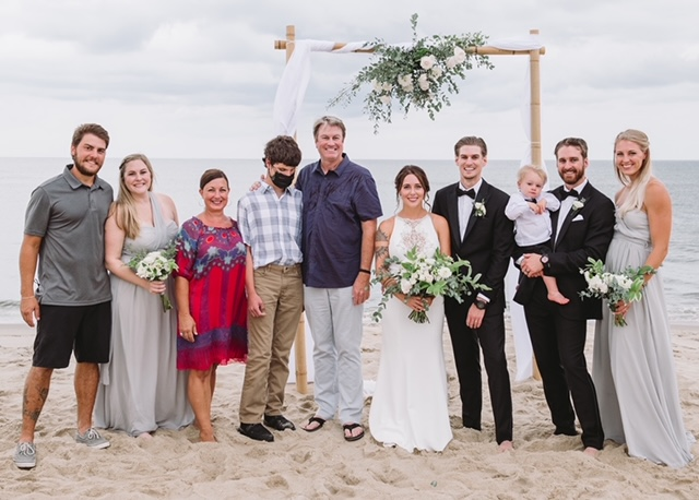 Thomas with his family at a wedding on the beach.