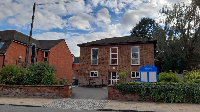 The front of Coventry Quaker meeting house, including the garden, welcome sign, telegraph pole, next door building