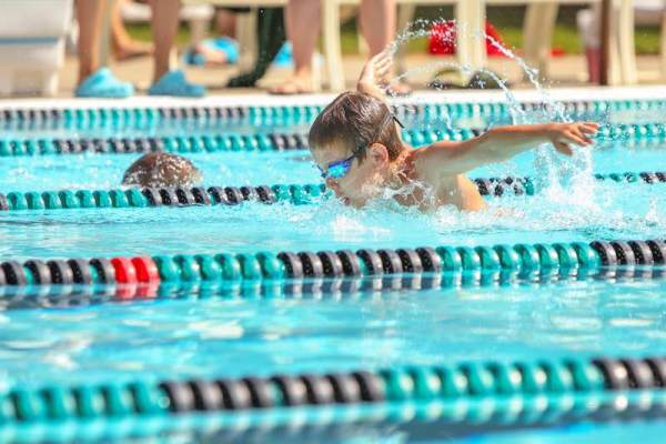 Boys competing with each other in a swim race.